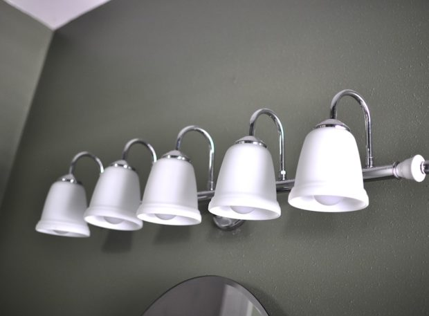 Clean white light fixtures hang above the bathroom sink