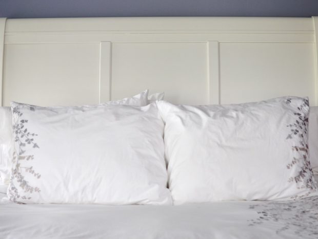 The bed frame is white and pillows are white while the walls are lavendar