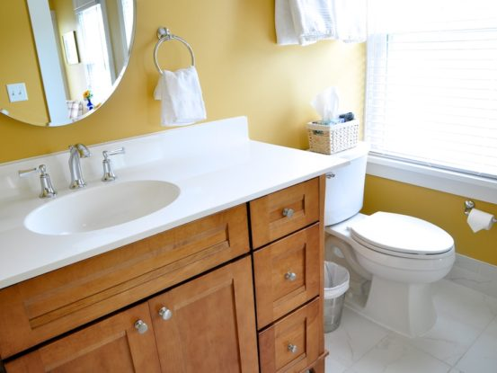 The bathroom inside the Spring Grove room is painted yellow with a nice clean white sink