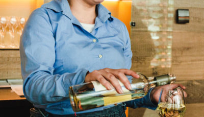 A woman pours a glass of wine to serve to patrons