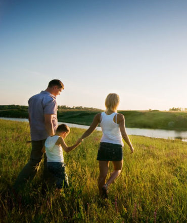 A family walks towards a lake in a field