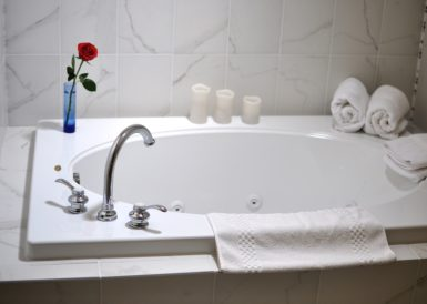 The Oakwood bathroom has a beautiful jacuzzi tub with a single rose for romance