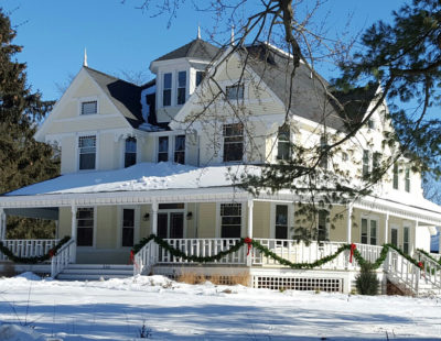 The exterior of the Greenway House in the winter is warm and inviting